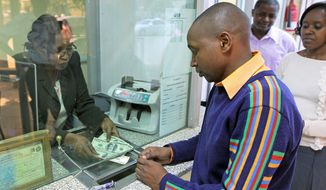 A Kenyan converts money at a currency-exchange bureau in Nairobi, Kenya, on Tuesday. Kenya's currency is in free fall against the dollar, dropping 30 percent in value this year, to an all-time low. That has increased prices of food and fuel across the country. (Associated Press)