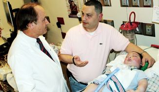 Moe Maraachli (center), with his son Joseph, reviews discharge plans with Dr. Robert Wilmott at Cardinal Glennon Children's Medical Center in St. Louis before leaving to return home to Ontario. Canada, in April. Joseph died Tuesday. (Photo via Associated Press)