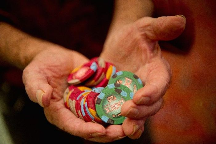 Bill Bregenzer of Flemington, N.J., shows off his winnings while standing in line for a cashier near the gambling floor last week in Parx Casino, near Philadelphia. (Andrew Harnik/The Washington Times)
