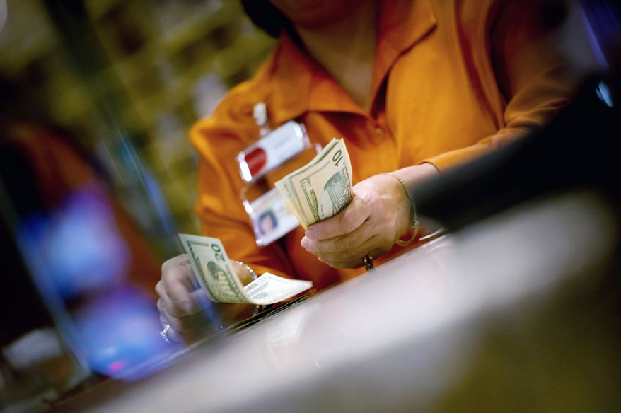 SHOW ME THE MONEY: A cashier counts some of the take at Parx Casino, one of the hot spots that have kept gamblers in Pennsylvania. Since 2006, state gambling taxes and licensing fees have generated billions of dollars and thousands of jobs. (Andrew Harnik/The Washington Times)