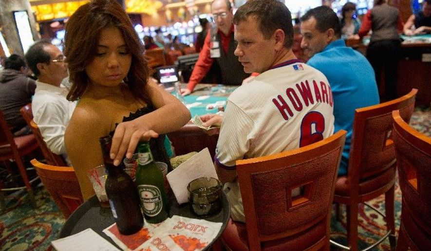 Republican Budget >> Darine Son, a cocktail waitress, serves beer to Bob Schank while he plays cards at a blackjack ...