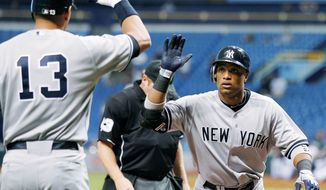 Robinson Cano (right) and the Yankees are guaranteed of opening an American League first-round series at home Friday night. (Associated Press)