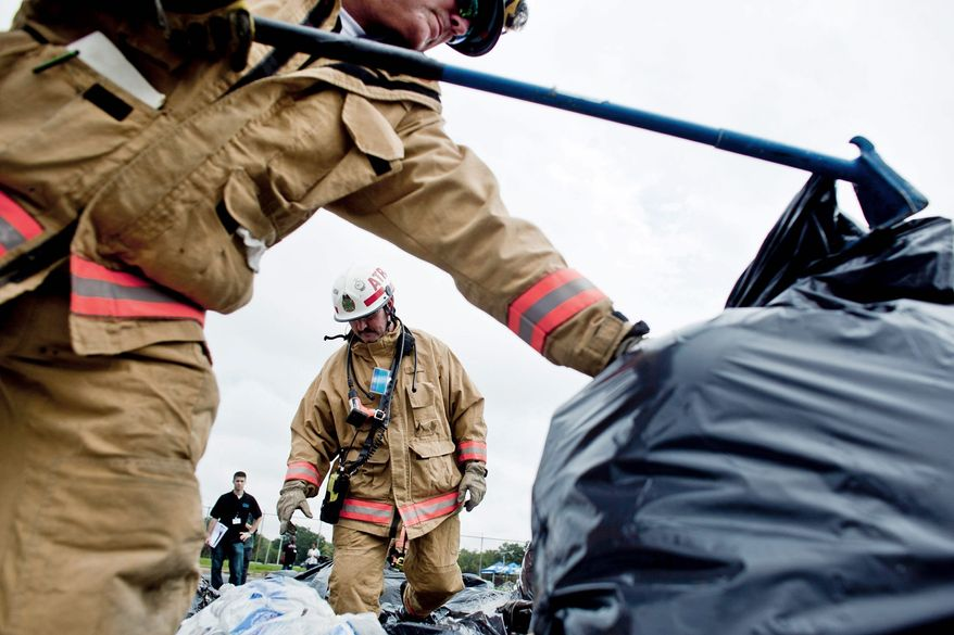 Lt. Greg Dypsky (foreground) and Fireman Steve Muccino (center), members of the Rescue Squad 3 Collapse Task Force, search through the mock rubble of a fallen building in search of survivors and bodies at RFK Stadium on Wednesday. Government agencies and their nongovernment partners simulated a response to a Category 2 hurricane strike. (T.J. Kirkpatrick/The Washington Times)