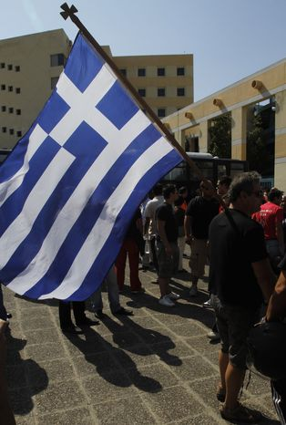A protesting taxi driver carries a Greek national flag in front of the transport ministry during a protest in Athens on Sept 28, 2011. About 2,000 striking taxi drivers gathered to protest against government plans to open up their licensed profession to more competition. (Associated Press)