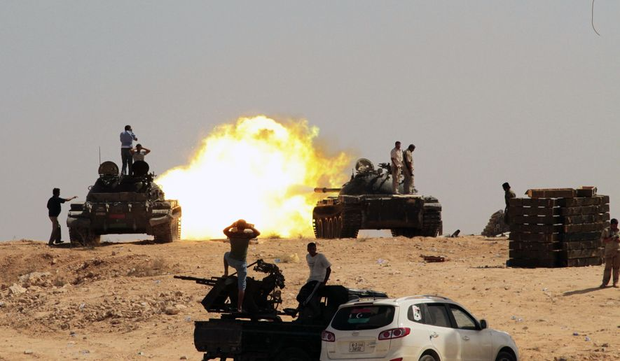 Libyan revolutionary fighters fire from tanks toward the positions of loyalists of Col. Moammar Gadhafi in Sirte, Libya, on Monday, Sept. 26, 2011. (AP Photo/Gaia Anderson)