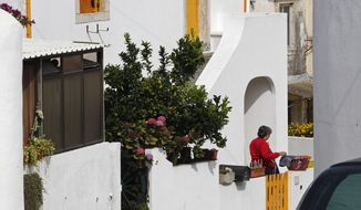 A woman who said she was Maria Do Rosario Valente, the wife of U.S. fugitive George Wright, is seen outside the house where neighbors said Wright lived in Almocagema, Portugal, near Lisbon, on Wednesday, Sept. 28, 2011.  (AP Photo/Francisco Seco)