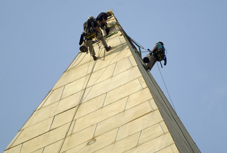 Dan Gach (left), Erik Shon (center) and Emma Cardini inspect the exterior of the Washington Monument for damage caused by last month's earthquake on Sept. 28, 2011. (Associated Press)