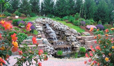 """Catherine and Spiro Alifrangis enjoy the waterfall in the backyard of their Herndon home in all four seasons. Mrs. Alifrangis said """"neighbors and visitors comment on it all the time."""""""