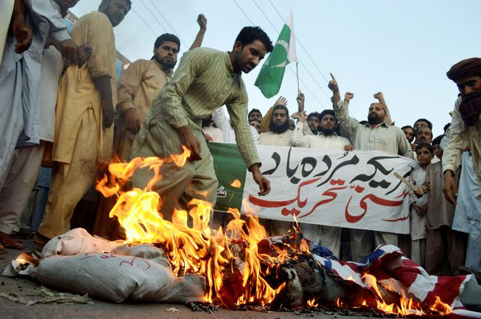 """Holding a banner that says """"Down with America,"""" Pakistani protesters burn a representation of the U.S. flag and an effigy of Navy Adm. Mike Mullen during an anti-American rally in Multan on Thursday. U.S. pressure on Pakistan to attack Afghan militants on its soil will not succeed, the prime minister said in response to Adm. Mullen's assertions that the army's spy agency is supporting insurgents. (Associated Press)"""