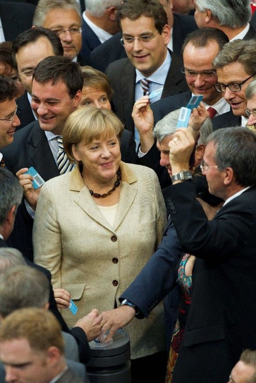 German Chancellor Angela Merkel casts her vote on the eurozone bailout fund at the Bundestag in Berlin on Thursday. German lawmakers approved new powers for the fund in a major step toward tackling the bloc's sprawling sovereign debt crisis. (Associated Press)