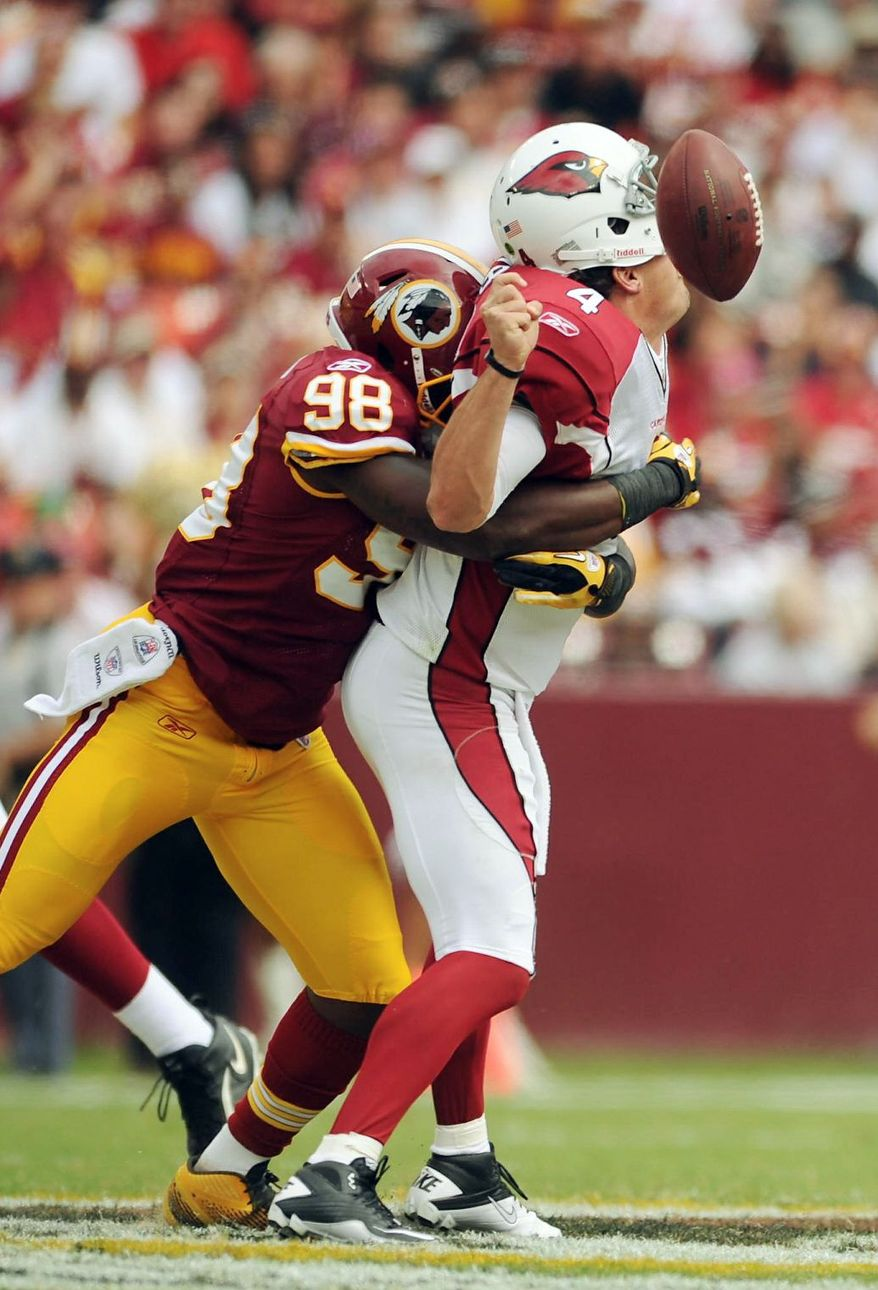 Redskins linebacker Brian Orakpo jars the ball from the grasp of Arizona quarterback Kevin Kolb while sacking him Sept. 18. Washington says it won't shy away from its blitzing schemes despite losing on a gamble Monday night. (Andrew Harnik/The Washington Times)