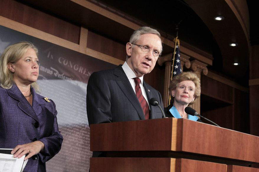 **FILE** Senate Majority Leader Harry Reid, Nevada Democrat, is joined by fellow Democrat Sens. Mary Landrieu (left) of Lousiana and Debbie Stabenow of Michigan on Sept. 26 2011, following the short-term funding bill vote on Capitol Hill. (Associated Press)