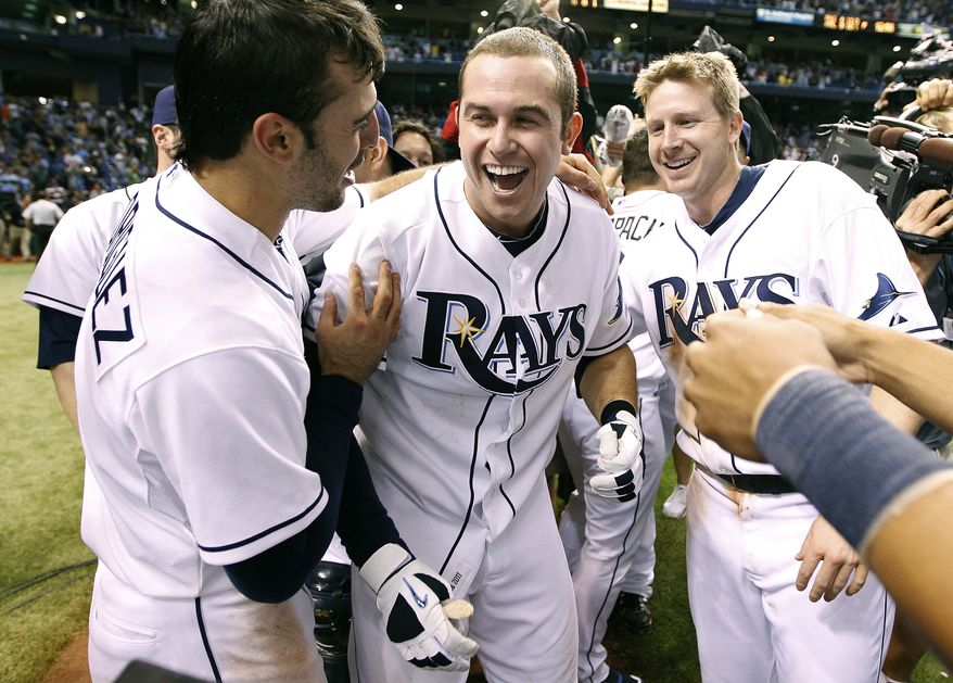 Tampa Bay Rays, from left, Sean Rodriguez, Evan Longoria, and Elliot Johnson celebrate clinching the AL Wild Card with an 8-7 win over the New York Yankees on Thursday, Sept. 29, 2011, in St. Petersburg, Fla. (AP Photo/Chris O'Meara)