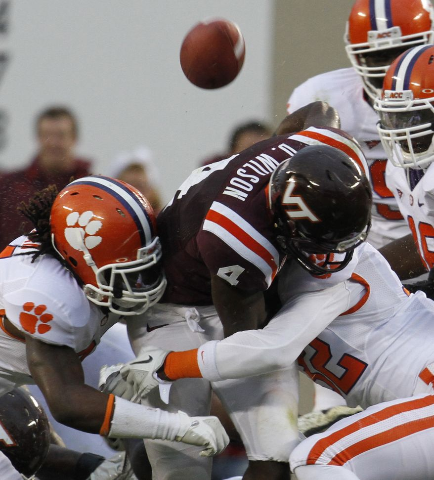 Virginia Tech running back David Wilson (4) loses the ball as he is tackled by Clemson linebacker Quandon Christian, left, and safety Carlton Lewis, right, during the first half of an NCAA college football game at Lane Stadium in Blacksburg, Va., Saturday, Oct. 1, 2011. (AP Photo/Steve Helber)