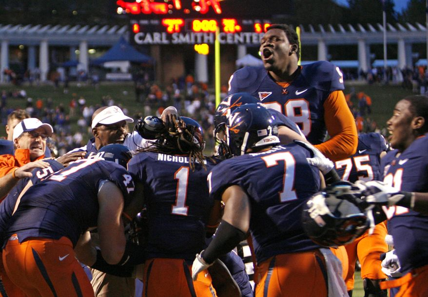 Virginia's Chris Brathwaite, top right, and other teammates celebrate their 21-20 overtime win over the Idaho in an NCAA college football game Saturday, Oct. 1, 2011, in Charlottesville, Va. (AP Photo/Richmond Times-Dispatch, P. Kevin Morley)
