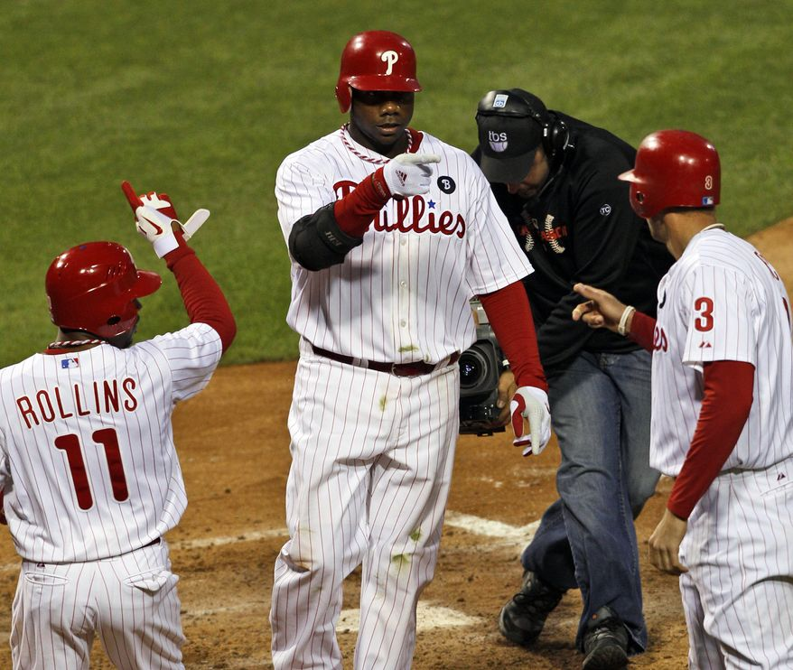 Philadelphia Phillies Ryan Howard, center, reacts with Jimmy Rollins, left, and Hunter Pence, after hitting a three-run home run in the sixth inning of Game 1 of baseball's National League division series against the St. Louis Cardinals, Saturday, Oct. 1, 2011, in Philadelphia. (AP Photo/Mel Evans)