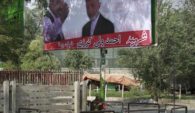 ** FILE ** An Afghan soldier takes position under a huge poster of Afghan President Hamid Karzai with his late brother Ahmad Wali Karzai, during a gun battle with militants in Kabul, Afghanistan on Tuesday, Sept. 13, 2011. (AP Photo/Musadeq Sadeq)