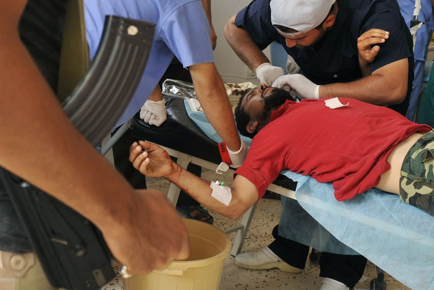 An injured Libyan revolutionary fighter is treated by medics in a field hospital outside Sirte, Libya, Friday, Sept. 30, 2011. Rebel forces are struggling to make headway against loyalist fighters inside the home town of Libya's ousted leader Moammar Gadhafi. (AP Photo/Bela Szandelszky)
