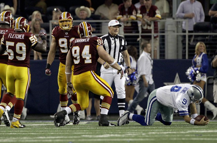 Dallas Cowboys quarterback Tony Romo (9) is slow to get up after a tackle by Washington Redskins defensive end Adam Carriker (94) during an NFL football game Monday, Sept. 26, 2011, in Arlington, Texas. (AP Photo/Tony Gutierrez)