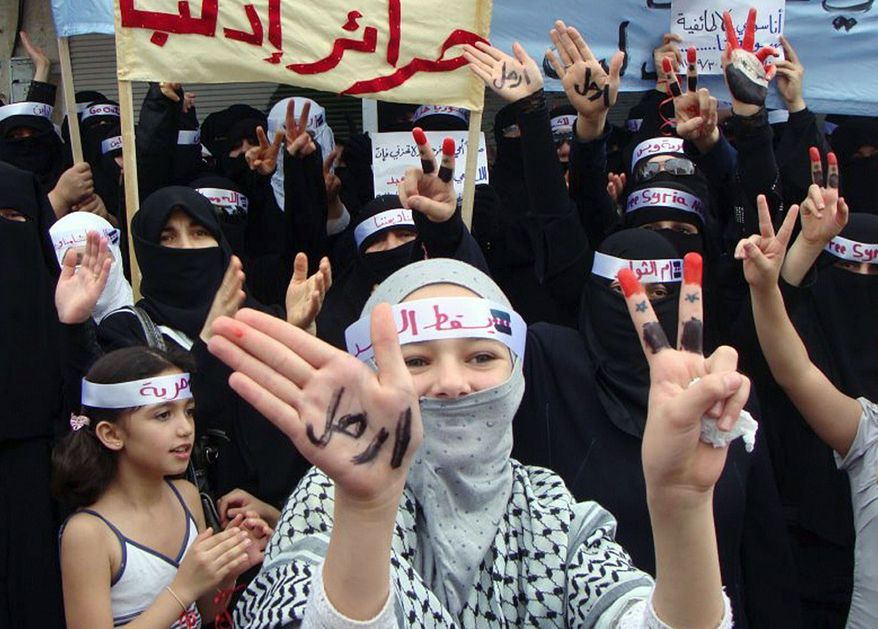"""In this citizen journalism image made with a mobile phone and provided by Shaam News Network, foes of Syrian President Bashar Assad flash victory signs as one woman displays one hand with the Arabic word reading: """"leave"""" during a demonstration Friday in Edlib province against the Syrian regime. (Associated Press)"""
