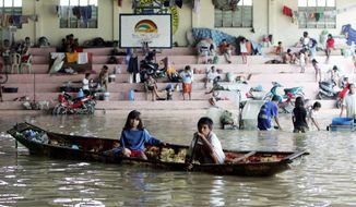 Storm victims keep themselves dry in a boat and on the steps of a flooded basketball court that serves as an evacuation center as flooding continues for the fourth day Sunday in Bulacan province north of Manila. Back-to-back typhoons left at least 59 people dead in the northern Philippines. (Associated Press)
