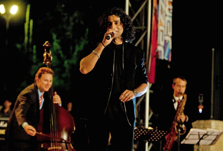 Pakistani singer Rameez Mukhtar (center) is accompanied by Ari Roland (left) and Chris Byars of the Ari Roland Jazz Quartet during a concert sponsored by the U.S. Embassy in Islamabad, Pakistan. The embassy also plans to bring over a country rock band and a hip-hop group. (Associated Press)