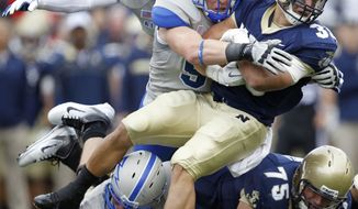 Navy fullback Alexander Teich, tight, is tackled by Air Force defensive lineman Harry Kehs during the second quarter of an NCAA college football game, Saturday, Oct. 1, 2011, in Annapolis, Md. Air Force won 35-34 in overtime. (AP Photo/Luis M. Alvarez)