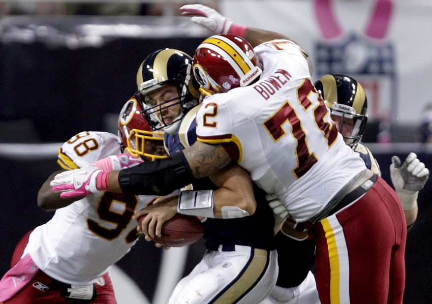 St. Louis Rams quarterback Sam Bradford is sacked for a 2-yard loss by Washington Redskins defenders Brian Orakpo and Stephen Bowen during the second quarter on Sunday, Oct. 2, 2011, in St. Louis. (AP Photo/Tom Gannam)