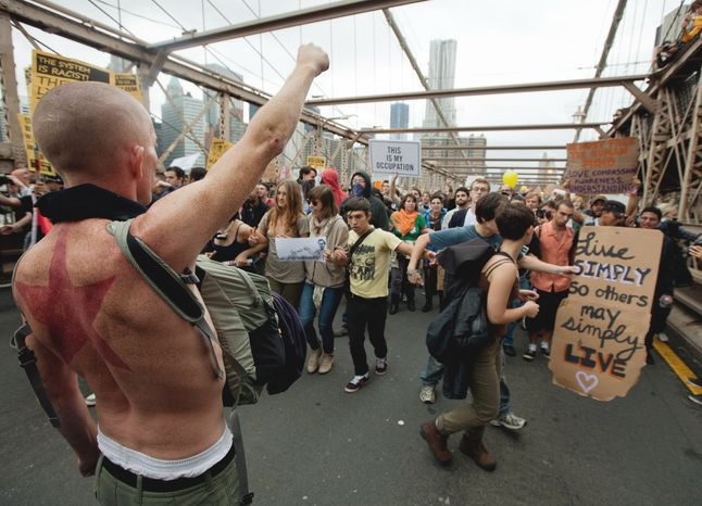 A large group of protesters affiliated with the Occupy Wall Street movement attempt to cross the Brooklyn Bridge, effectively shutting parts of it down, Saturday, Oct. 1, 2011, in New York. Police arrested dozens while trying to clear the road and reopen for traffic. (AP Photo/Will Stevens)