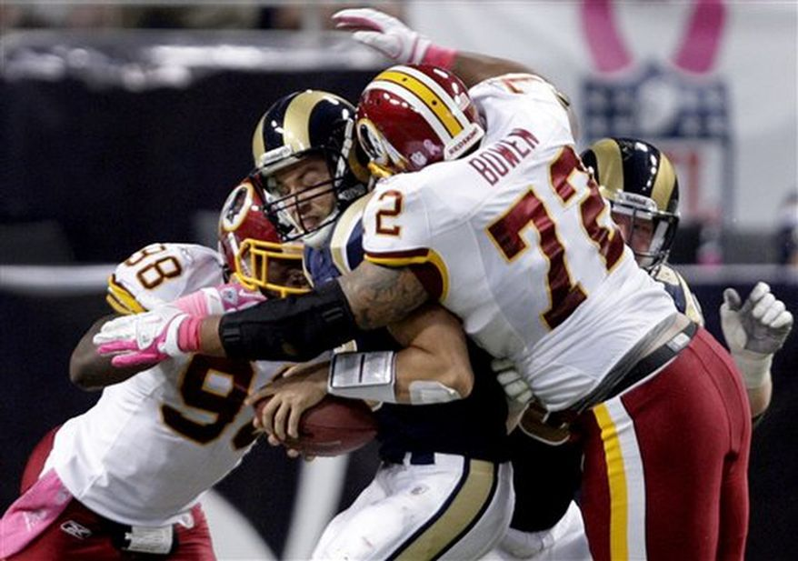 St. Louis Rams quarterback Sam Bradford, center, is sacked for a 2-yard loss by Washington Redskins defenders Brian Orakpo, left, and Stephen Bowen during the second quarter of the NFL football game Sunday, Oct. 2, 2011, in St. Louis. (AP Photo/Tom Gannam)