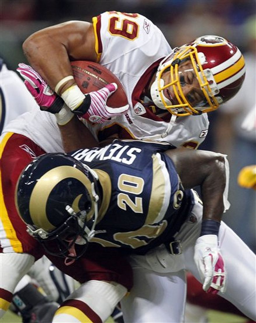 Washington Redskins running back Roy Helu, top, runs for a 2-yard gain before being brought down by St. Louis Rams safety Darian Stewart during the first quarter of the NFL football game Sunday, Oct. 2, 2011, in St. Louis. (AP Photo/Jeff Roberson)
