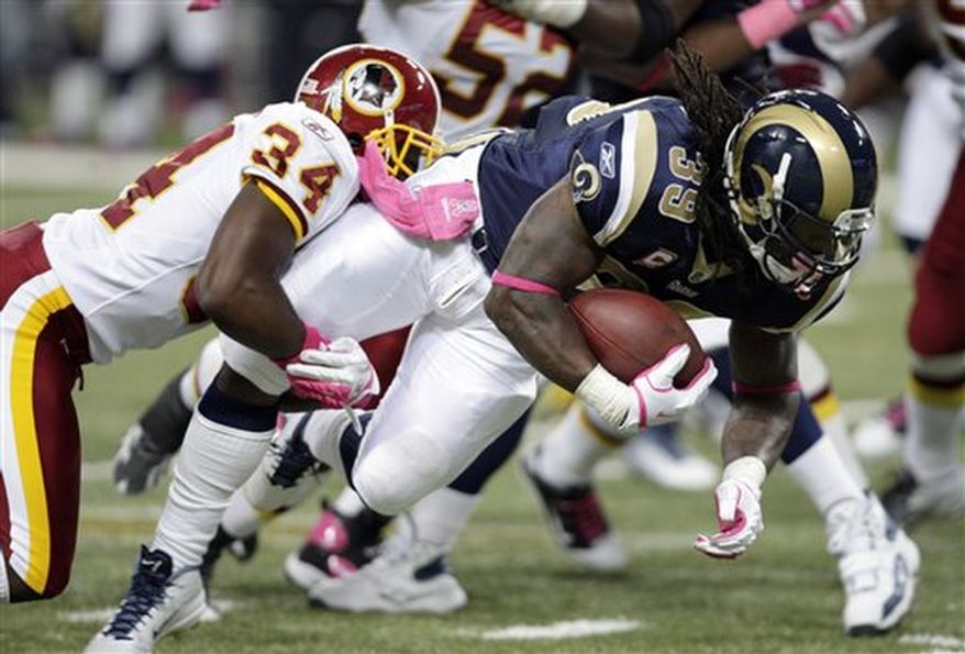 St. Louis Rams running back Steven Jackson, right, runs for a 3-yard gain before being brought down by Washington Redskins cornerback Byron Westbrook during the second quarter of the NFL football game Sunday, Oct. 2, 2011, in St. Louis. (AP Photo/Tom Gannam)