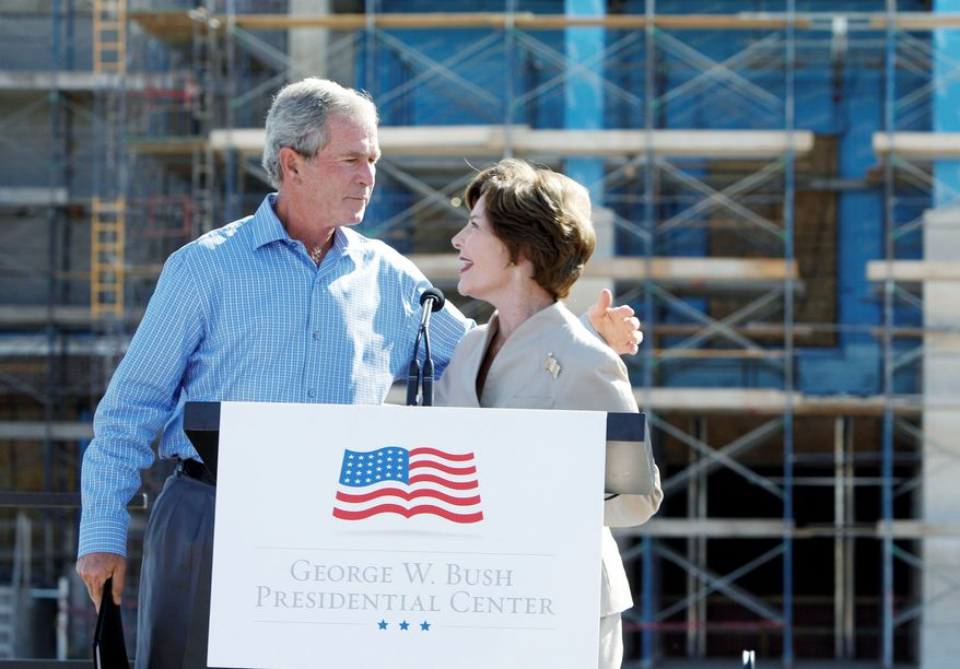 """** FILE ** Former first lady Laura Bush introduces her husband, former President George W. Bush, at the """"topping out"""" ceremony of his library on the campus of Southern Methodist University in Dallas. (Associated Press)"""