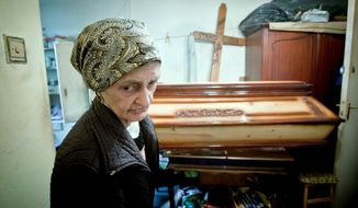 Elena Stancu, here in July, keeps in her Bucharest apartment a coffin and cross the 75-year-old Romanian bought with her savings. Times are so hard in Romania that people seek out carpenters selling cut-rate coffins in an effort to beat the rising costs of death. (Associated Press)