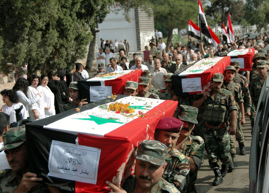 Syrian army soldiers carry the coffins of comrades killed in recent violence in the country during a funeral procession on Oct. 1, 2011, at the military hospital in Homs, Syria. (Associated Press/SANA)