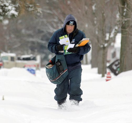 **FILE** A Postal Service letter carrier delivers mail in the snow in Berea, Ohio. (Associated Press)