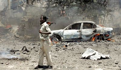 """A soldier keeps guard near burned bodies and a smoldering vehicle at the scene of Tuesday's explosion in Mogadishu, Somalia, when a car laden with explosives blew up in front of the Ministry of Education. """"The casualties are mostly students and parents who were waiting for results of scholarships,"""" the government said. (Associated Press)"""