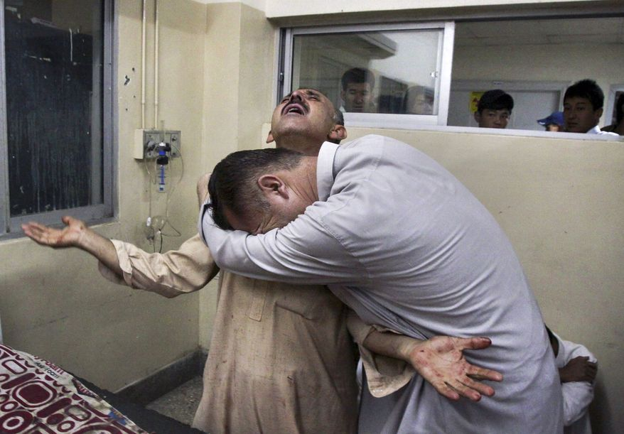 Pakistanis mourn Oct. 4, 2011, at a local hospital in Quetta, Pakistan, the death of a relative killed in a firing incident. Suspected Sunni extremists opened fire on Shiite Muslims traveling through southwestern Pakistan, killing scores of people and wounding six others in the latest apparent sectarian attack to plague the country, police said. (Associated Press)