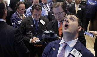 Specialist Michael Gagliano (right, in foreground) calls out prices at his post on the floor of the New York Stock Exchange on Oct. 4, 2011. (Associated Press)