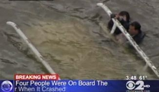 In this frame grab image taken from WCBS-TV, survivors cling to the bottom of a helicopter after it inverted following a crash in the East River in New York on Oct. 4, 2011. (Associated Press/WCBS-TV)