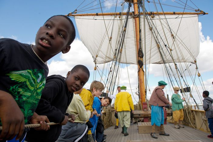 4th Graders Alhaji Conteh, left, and Alhaji Sesay, second from left, from James Polk Elementary School in Alexandria learn how to turn a sail with the help of their classmates aboard the Godspeed. (Andrew Harnik / The Washington Times)