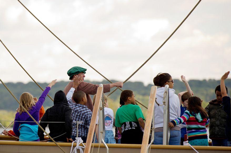 Volunteer ships crew member Pete Moxon, center left, of Williamsburg, VA teaches 4th graders from James Polk Elementary School in Alexandria, VA how to navigate aboard the Godspeed. (Andrew Harnik / The Washington Times)