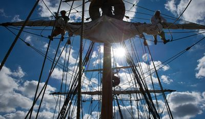 Volunteer crew members John Robinson, left, of Hampton, VA, and Steve Link, right, of Williamsburg, VA put away the main sail aboard the Godspeed. (Andrew Harnik / The Washington Times)