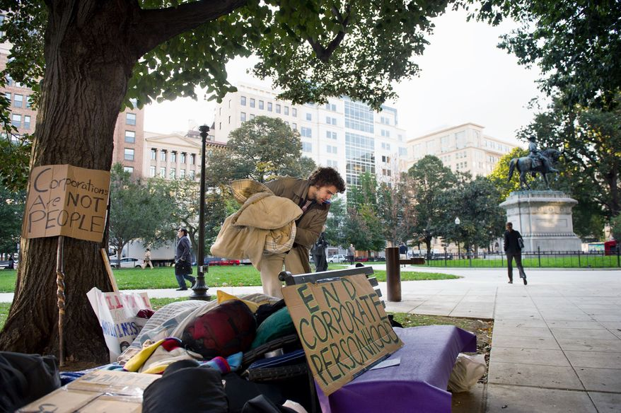 """Eric Sponaugle of Olney packs up his blanket Wednesday morning after sleeping near McPherson Square as part of the """"Occupy D.C."""" protest. The protesters' complaints - corporate greed, corruption and social injustice - are vaguely defined, but they attract a wide swath of disaffected supporters. (Andrew Harnik/The Washington Times)"""