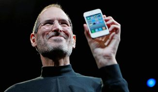 "Apple founder Steve Jobs holds a new iPhone at the Apple Worldwide Developers Conference in San Francisco in June 2010. Apple on Wednesday was ""deeply saddened to announce"" Mr. Jobs' death. He was 56. (Associated Press)"
