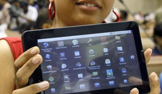 An Indian student poses with the supercheap Aakash tablet computer, which she received during its launch in New Delhi on Oct. 5, 2011. The $35 basic touch screen tablet aimed at students can be used for functions like word processing, web browsing and video conferencing. (Associated Press)
