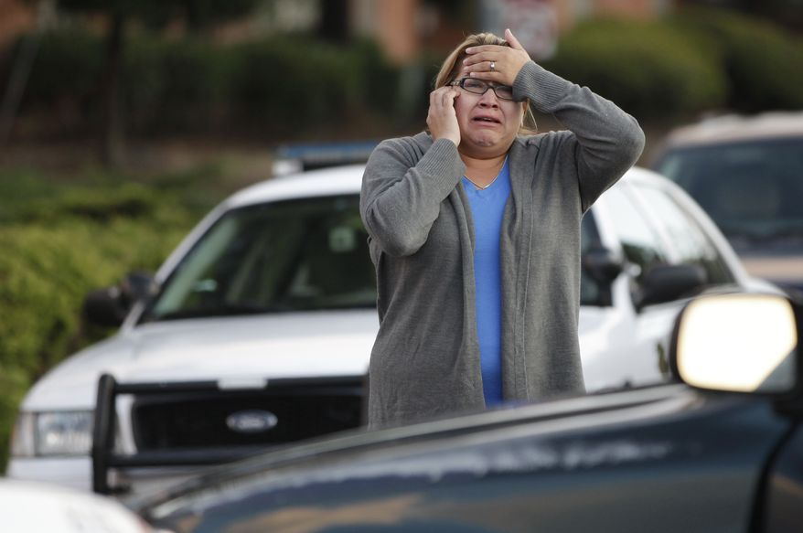 A woman who did not want to give her name reacts as she waits to hear about her father, who works at the Lehigh Southwest Cement Co. in Cupertino, Calif., on Wednesday, Oct. 5, 2011. Authorities say a disgruntled employee opened fire at a meeting at the plant, killing two people and wounding six others. (AP Photo/Paul Sakuma)