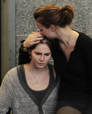 Amanda Knox (left) is comforted by her sister, Deanna Knox, during a news conference shortly after her arrival at Seattle-Tacoma International Airport on Oct. 4, 2011. (Associated Press)