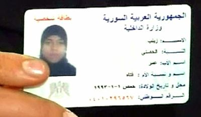 In this video grab photo released Oct. 4, 2011, by the Syrian official news agency SANA, A woman claiming that she is Zainab al-Hosni who the Human rights groups, including Amnesty International, and Syrian activists reported last month that was found dead and mutilated after she was detained in her hometown of Homs, shows her ID card during an interview with the Syrian state television, in Damascus, Syria. (Associated Press/SANA)