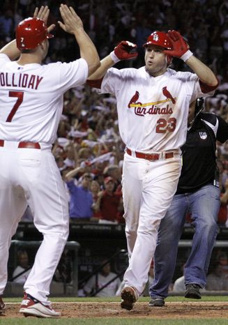 St. Louis Cardinals' David Freese, right, is congratulated by teammate Matt Holliday after hitting a two-run home run during the sixth inning of Game 4 of baseball's National League division series against the Philadelphia Phillies, Wednesday, Oct. 5, 2011, in St. Louis. (AP Photo/Jeff Roberson)